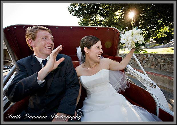 As they ride in horse drawn carriage the bride and groom wave to guests