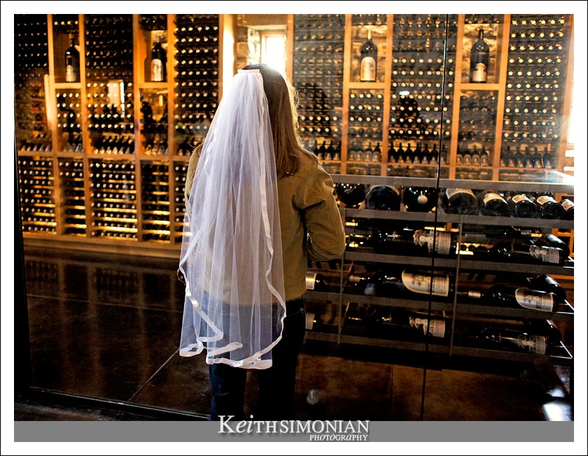 Cassie wearing her veil looks into the wine display room at Silver Oak Cellars.