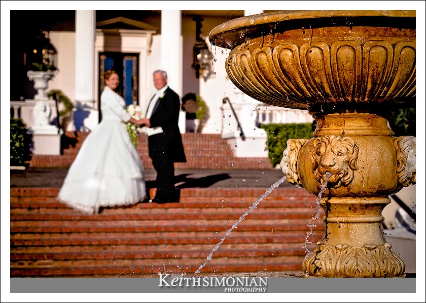 The happy couple pose outside the mansion with the water fountain in the foreground.
