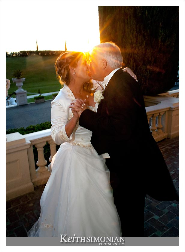 The sun sets behind the couple as they kiss.
