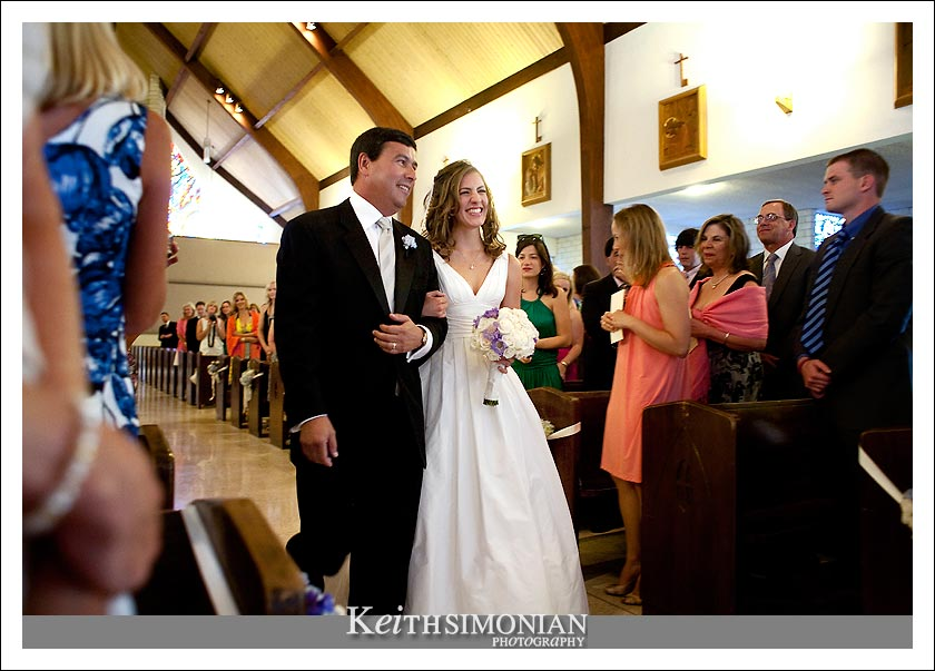 The bride and her father walk up the church isle