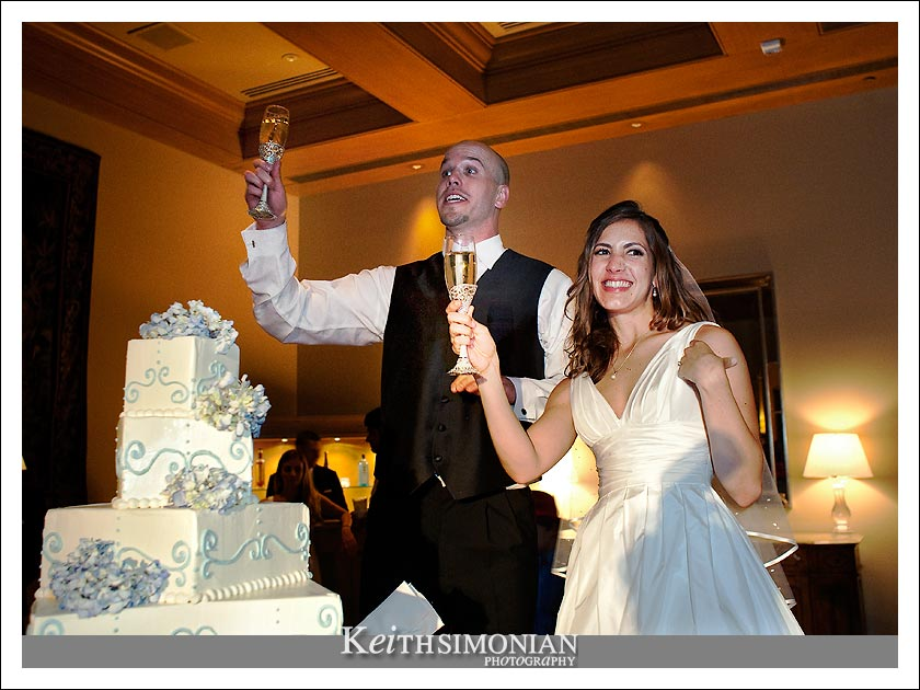 Cassie and Ben make a toast before cutting the 5 tier wedding cake