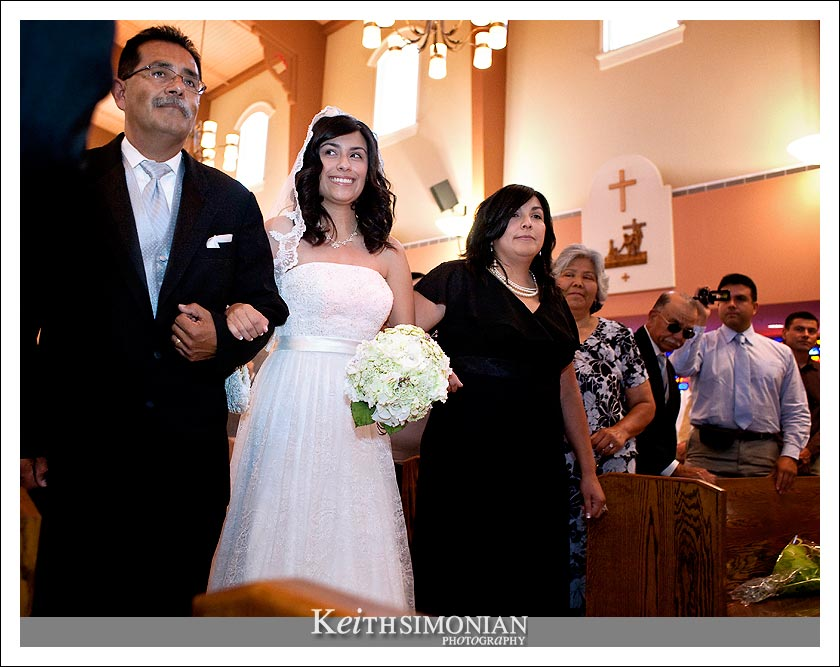 Bridgett walks up the aisle with her mother and father