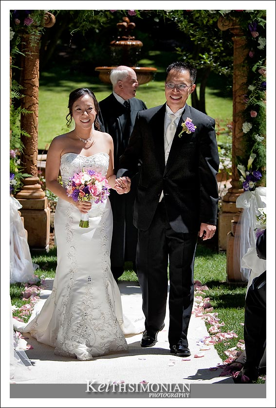 Ngoc and Vince walk down the isle as husband and wife.