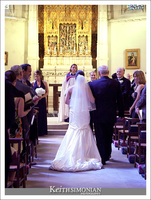 The bride walks down the isle with her father as the smiling groom waits at the alter