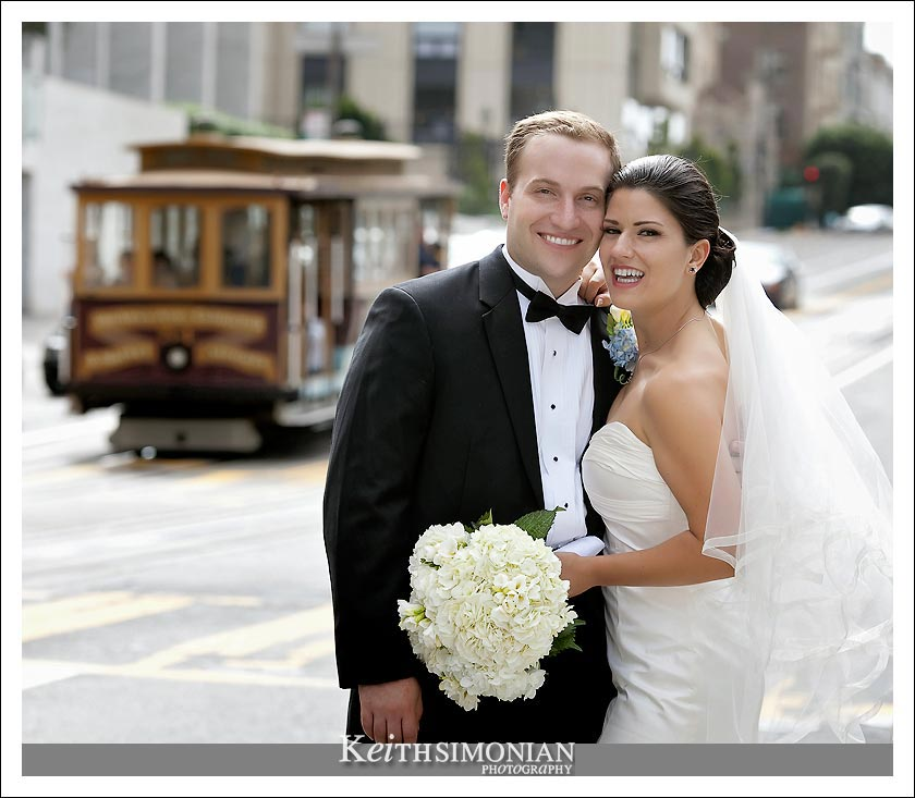 The Bride and Groom pose in front of passing cable car on California Street in San Francisco