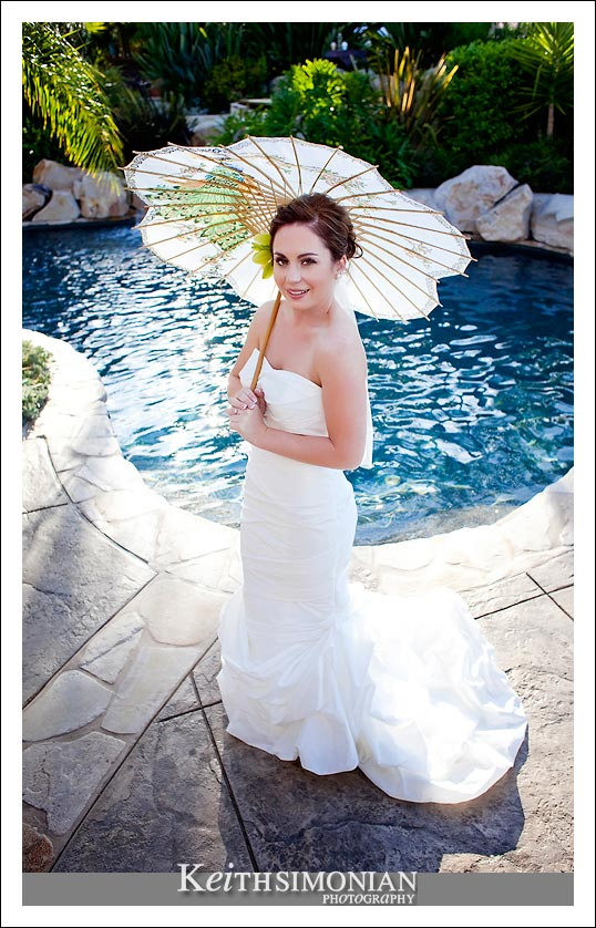 A Bride, a swimming pool, and an umbrella photo