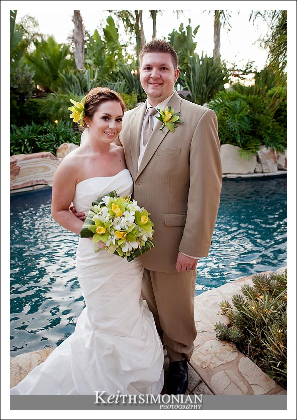 The bride and groom pose in front of the swimming pool