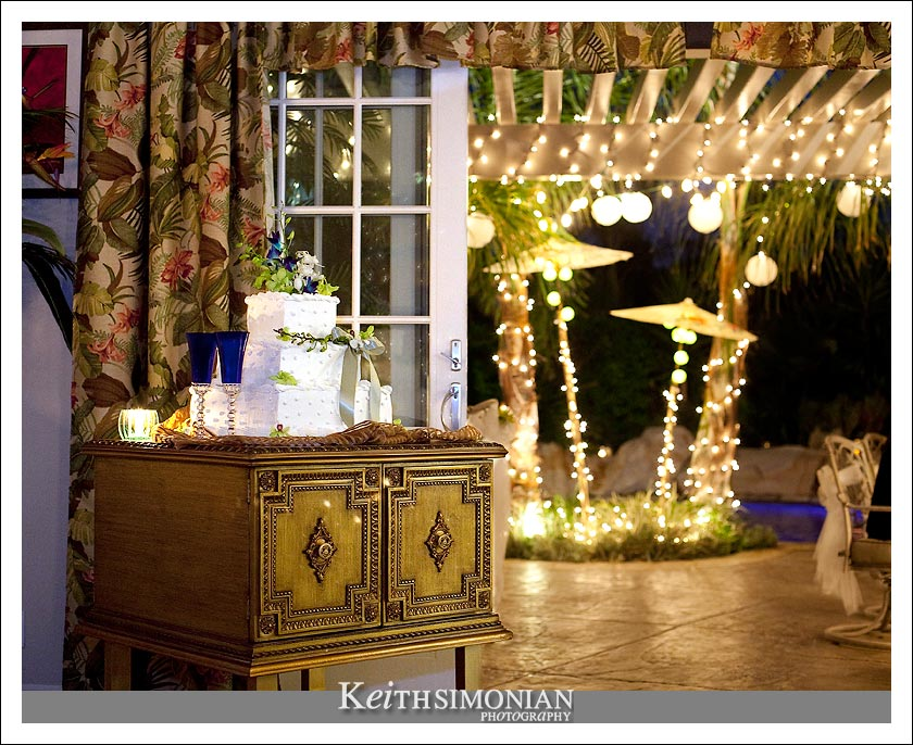 The wedding cake and the lights that decorate the backyard