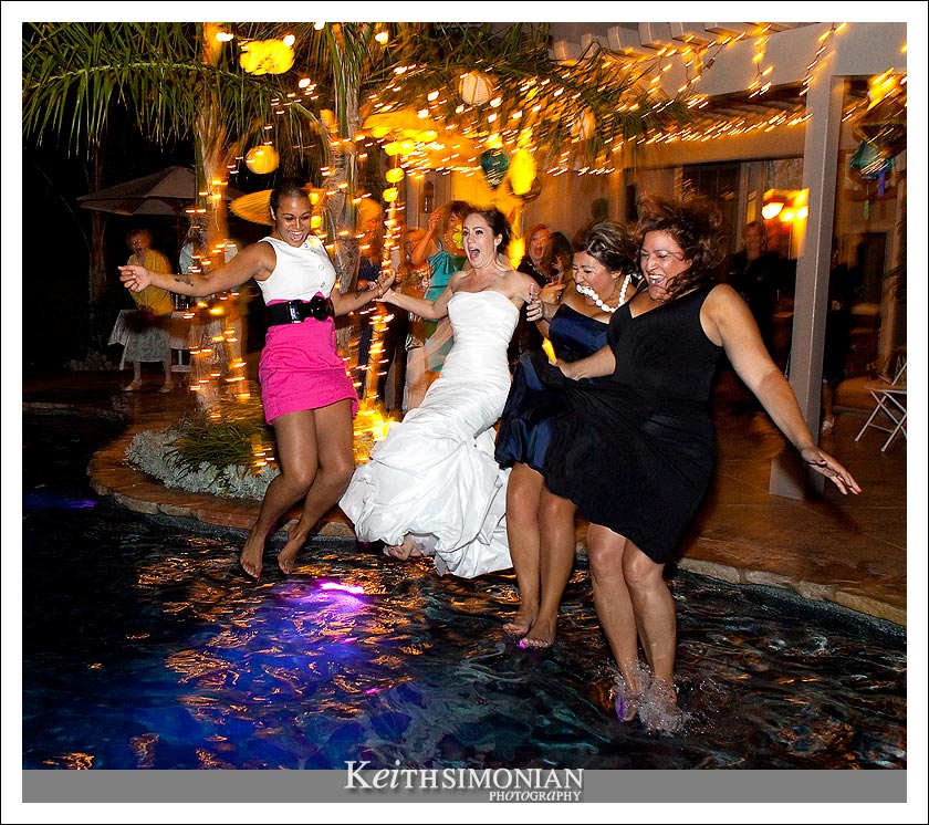 The bride, a bridesmaid, and a couple friends trash their dresses by jumping into the swimming pool