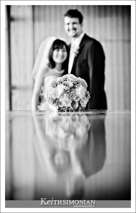 A black and white image showing a reflection of the bride and groom