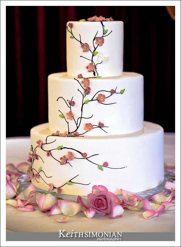 The wedding cake with pink flowers surrounding it