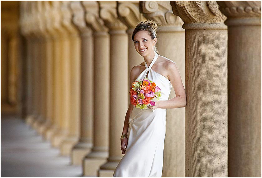 Bride poses with her bouquet in the row of columns at the Stanford Memorial church in Palo Alto