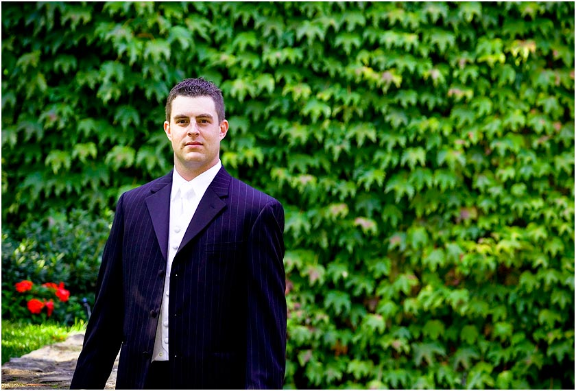 Groom in front of ivy covered wall at the Hughes Family Vineyard in the Napa Valley