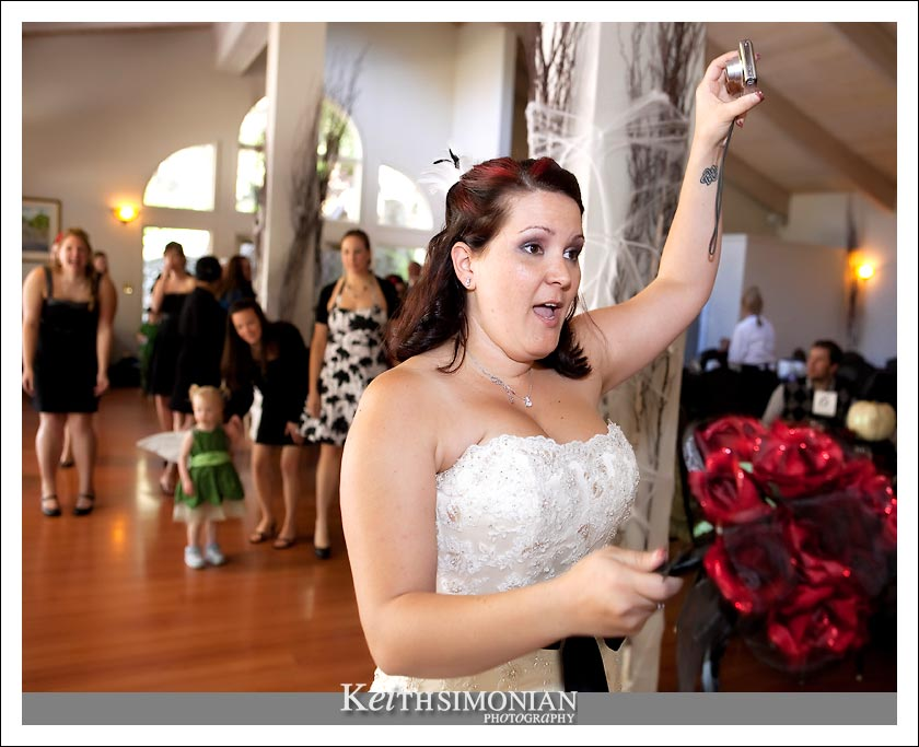 Not wanting to miss any of the action, the bride holds up her camera to capture the bouquet toss