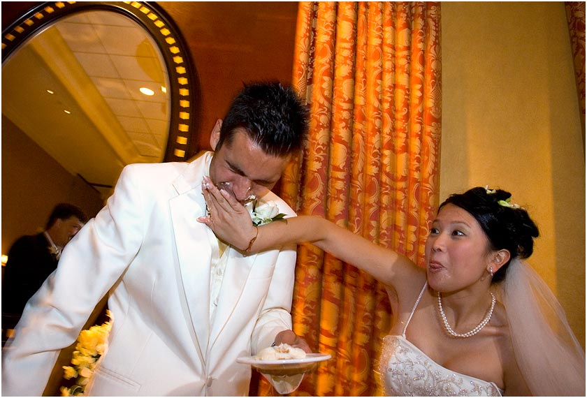 Bride smashes some cake on the groom at the Cypress Hotel in Cupertino, CA