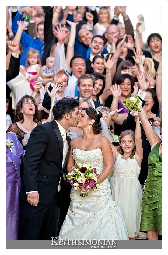 Bride and Groom kiss during group photo with all the guests