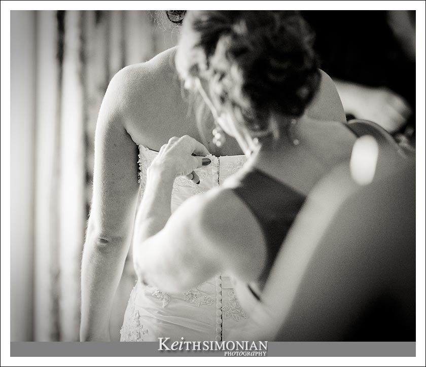 Mom puts the finishing touch on the bride's dress