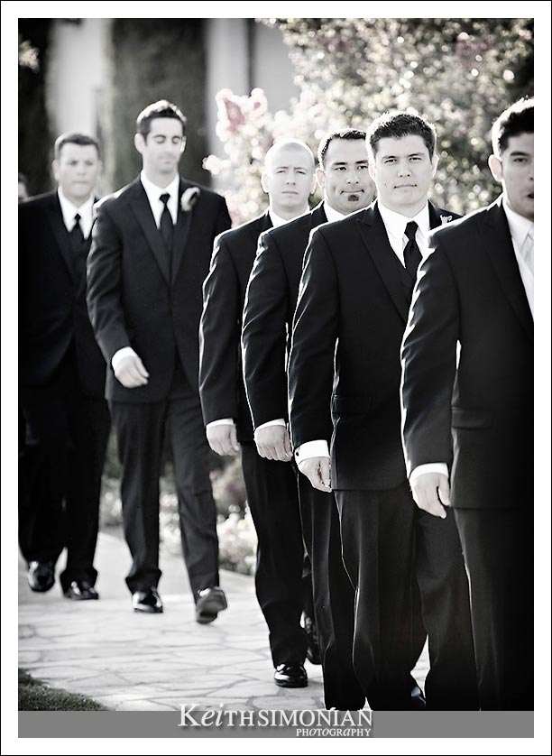 Black and white photo of the groom followed by the groomsmen