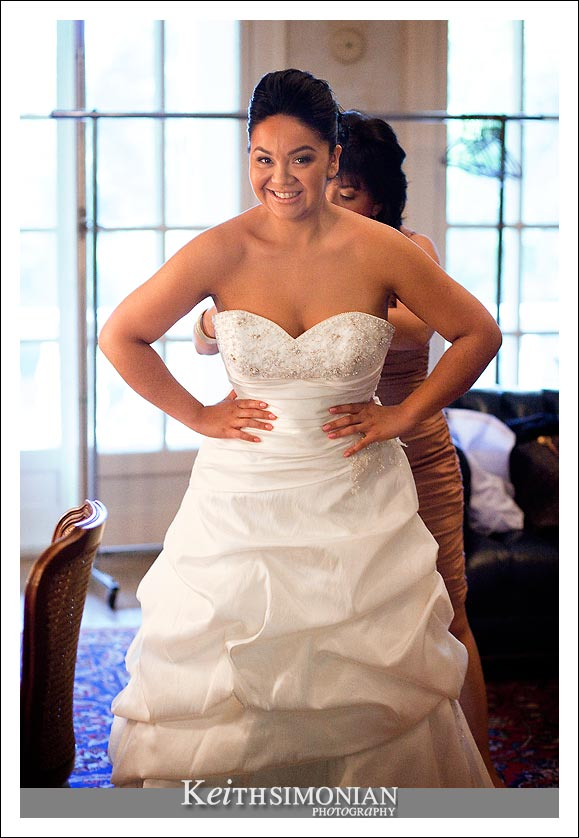 Bride getting into her white wedding dress