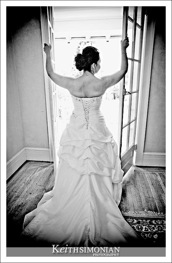 Black and white bridal portrait of the bride standing in front of the window