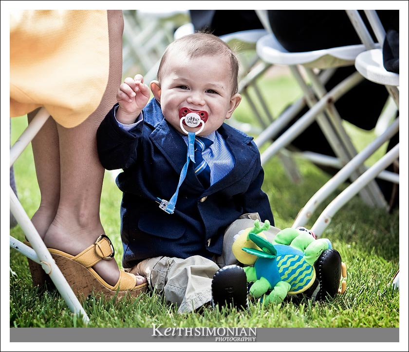 The happy young lad waves to the wedding photographer