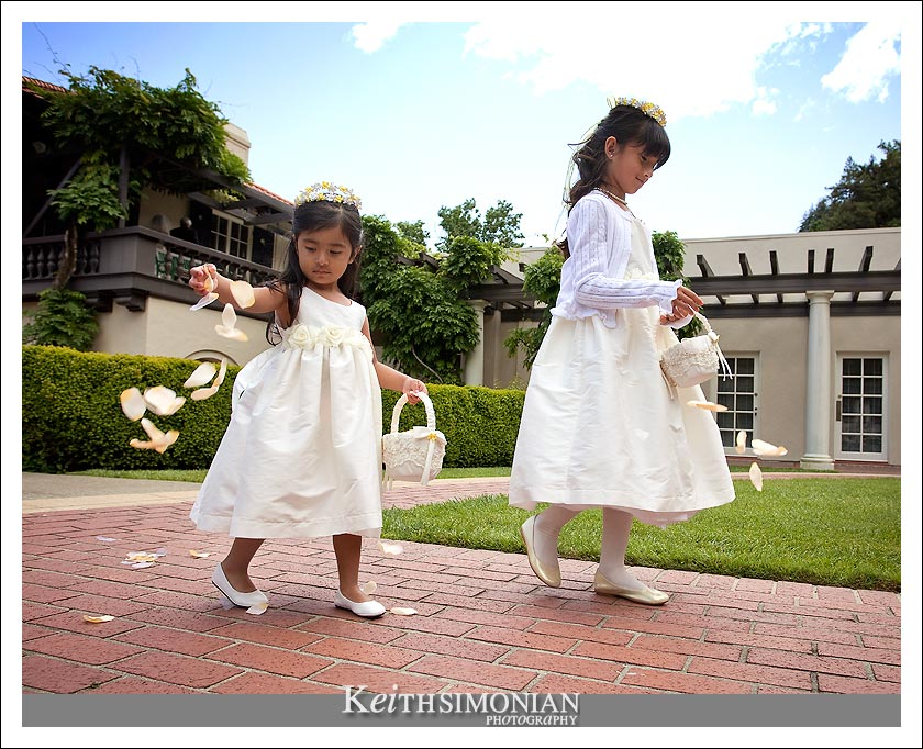 The flower girls the flower pedals on the brick walkway in this photo