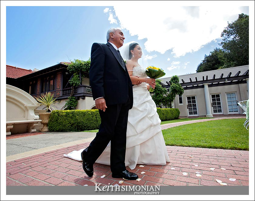 The father of the bride escorts her up the brick pathway