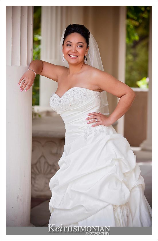 The sassy bride leans on the white column in this photo