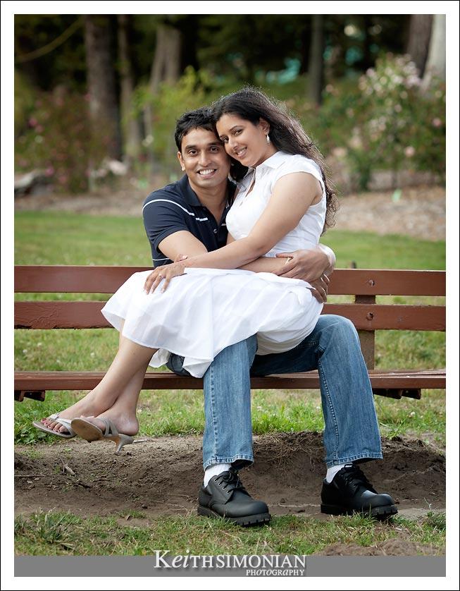 Bride sitting groom's lap in park