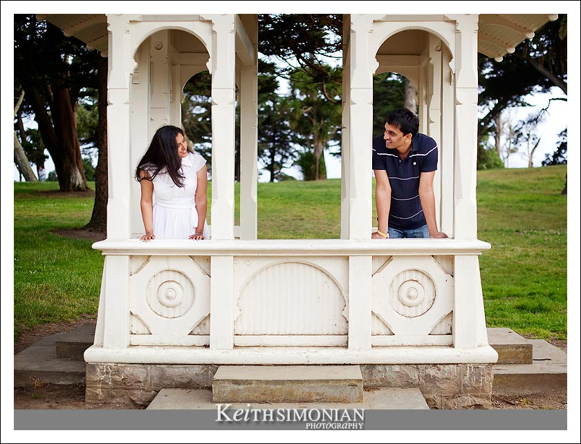 Couple pose in park structure during engagement photos