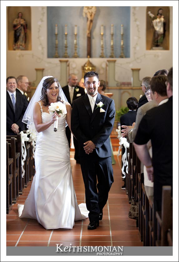 Bride and groom walk down the aisle after just getting married at the San Carlos Cathedral in Monterey, CA