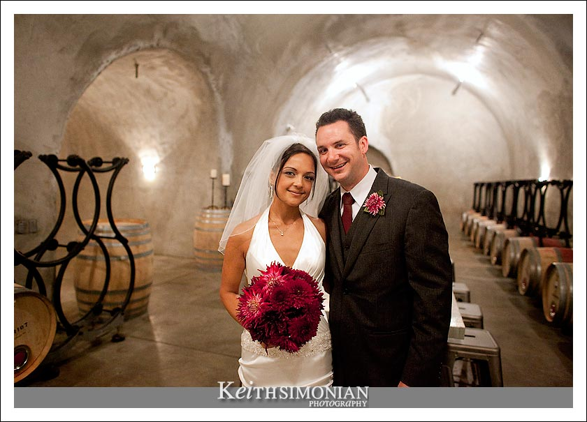 The bride and groom take a photo in the cave at the Caldwell Vineyard - Napa Valley California