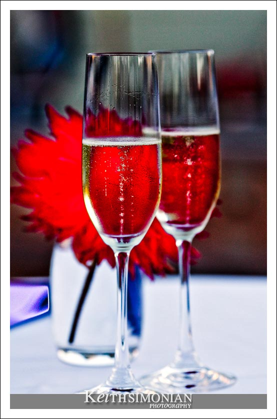 The red flower behind the champagne glasses give the champagne a red color