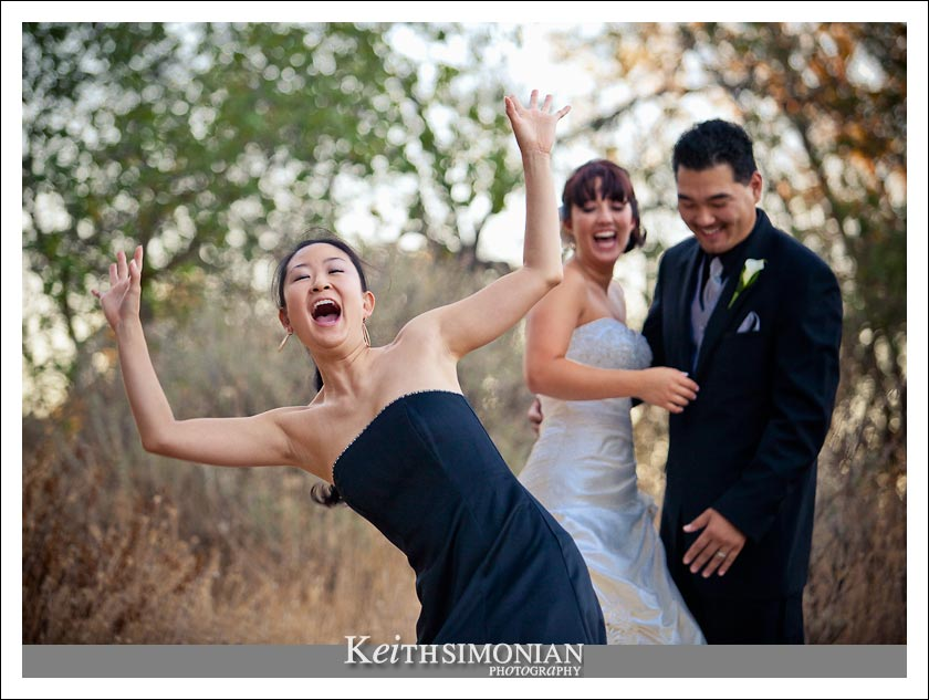 One of the bridesmaids has fun in front of the bride and groom