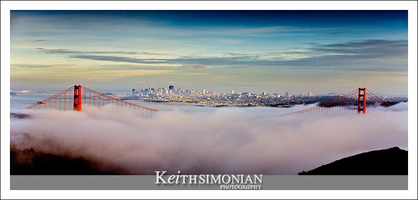 Fog covers the base of the Golden Gate Bridge with San Francisco skyline in the background of this photo