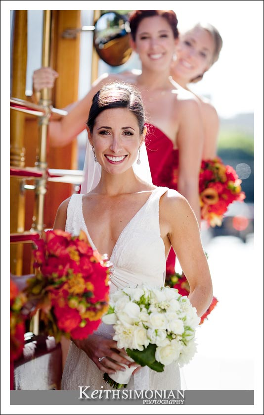 Bride on the side of cable car with her bridesmaids in red dresses