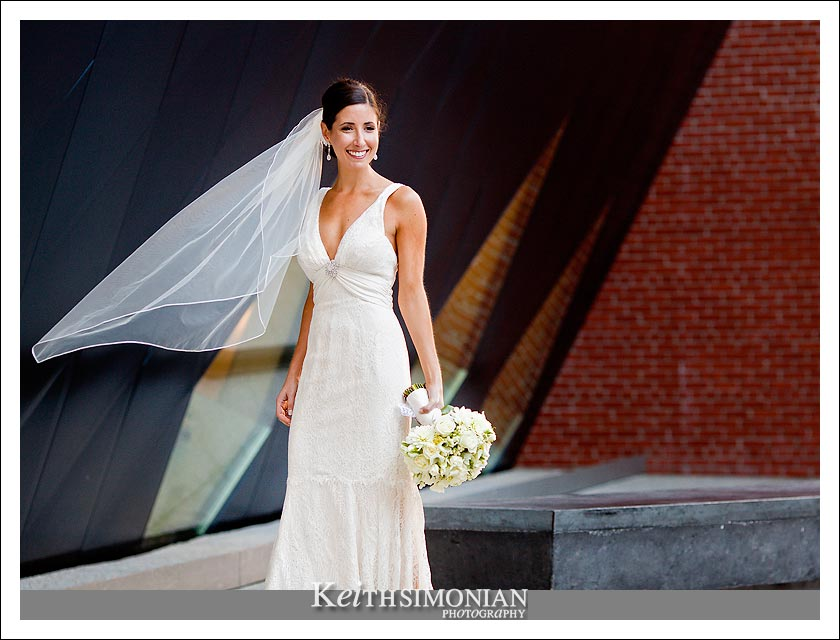 Photo of Bride with bouquet in front of brick building
