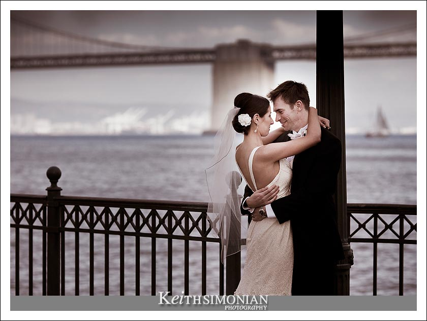Photo showing the bride and groom on pier with Oakland - San Francisco Bay Bridge in the background