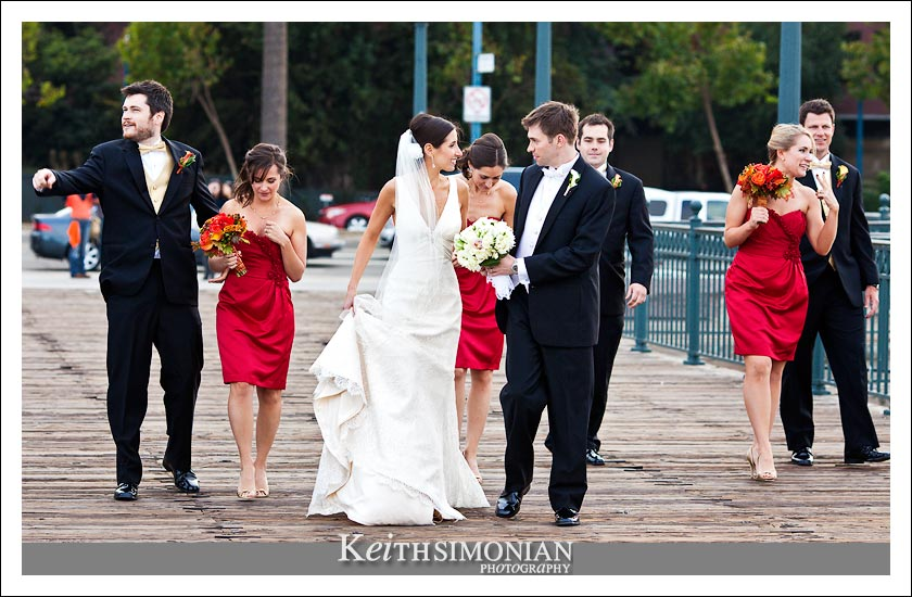 The bridal party walks along the San Francisco pier