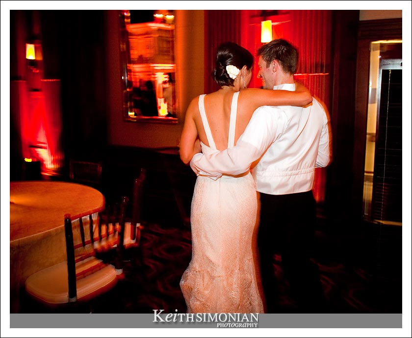 A slow shutter speed in this photo causes the slight blur and the bride and groom walk in the Julia Morgan ballroom in San Francisco