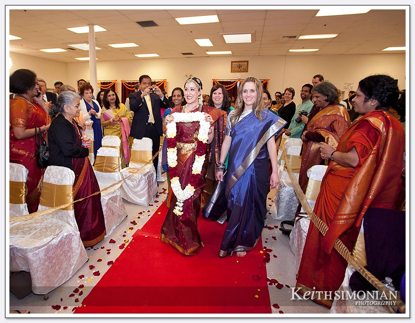 The bride carrying a red and white garland for the groom walks on the red carpet at the Shiva-vishnu Temple in Livermore, CA
