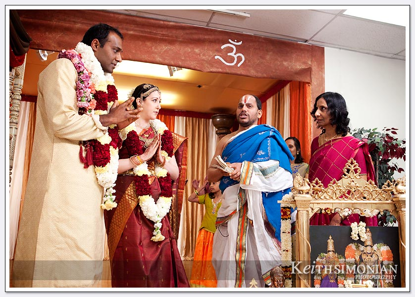 The couple wearing their garlands listen to the priest during the South Indian Hindu wedding ceremony at the Shiva-Vishnu Temple in Livermore, California