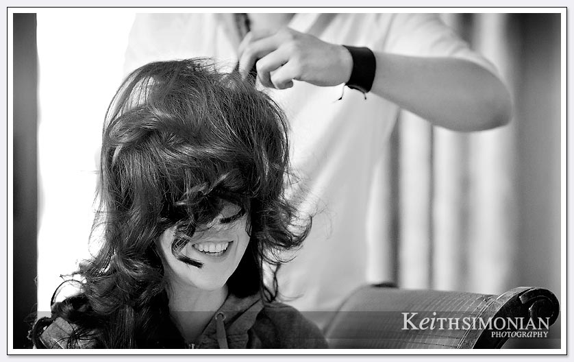 In this black and white photo the bride his having her hair done by the stylist at the Newark Fremont Hilton Hotel