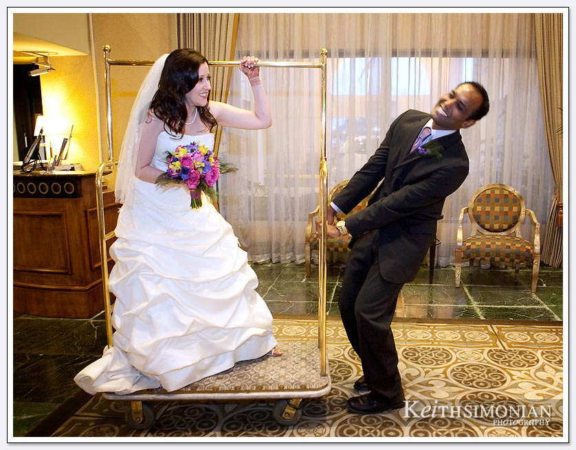 The bride and groom have a little fun with the hotel's luggage cart at the Newark/Fremont Hilton Hotel