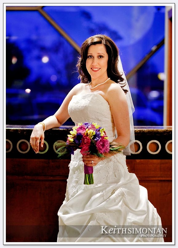 The bride poses for a formal portrait in front of a blue window with her bouquet at the Fremont/Newark Hotel