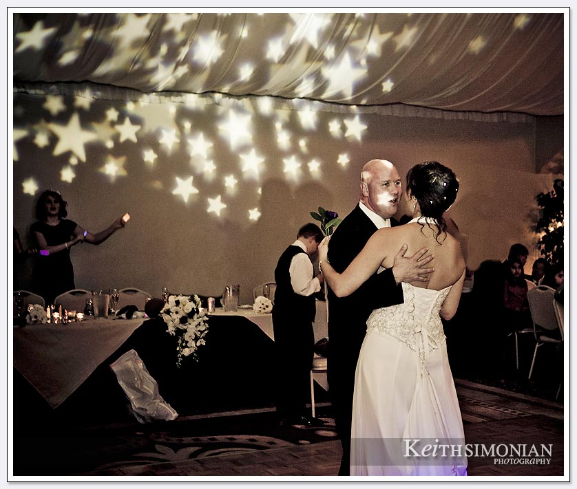 Stars are projected on the ceiling as the bride and groom share their first dance