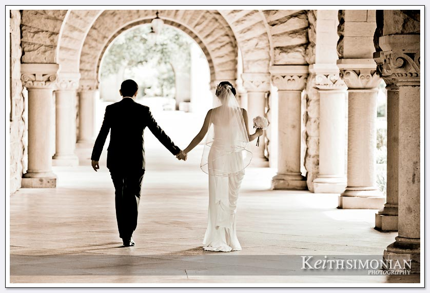 Black and white photo with bride and groom holding hands