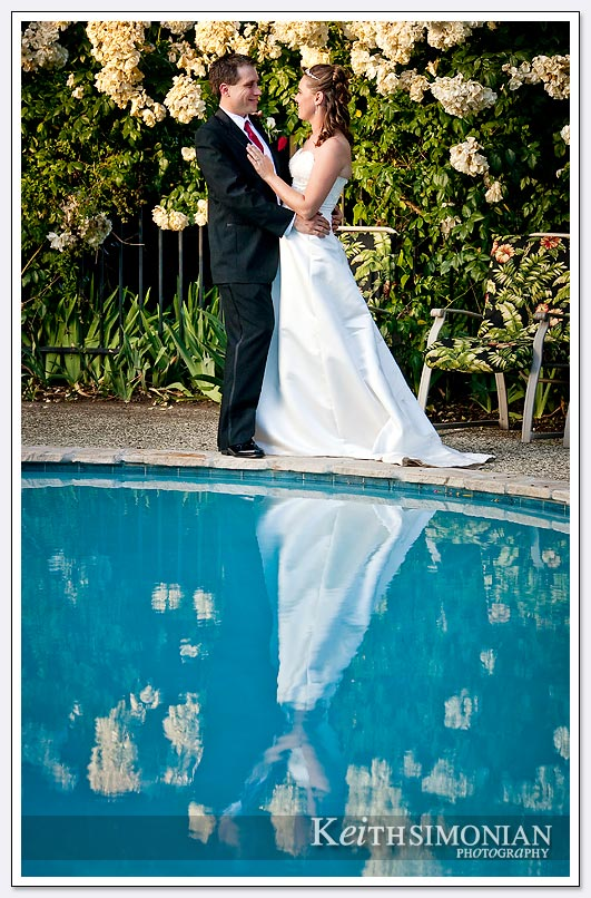 bride and groom by swimming pool photo