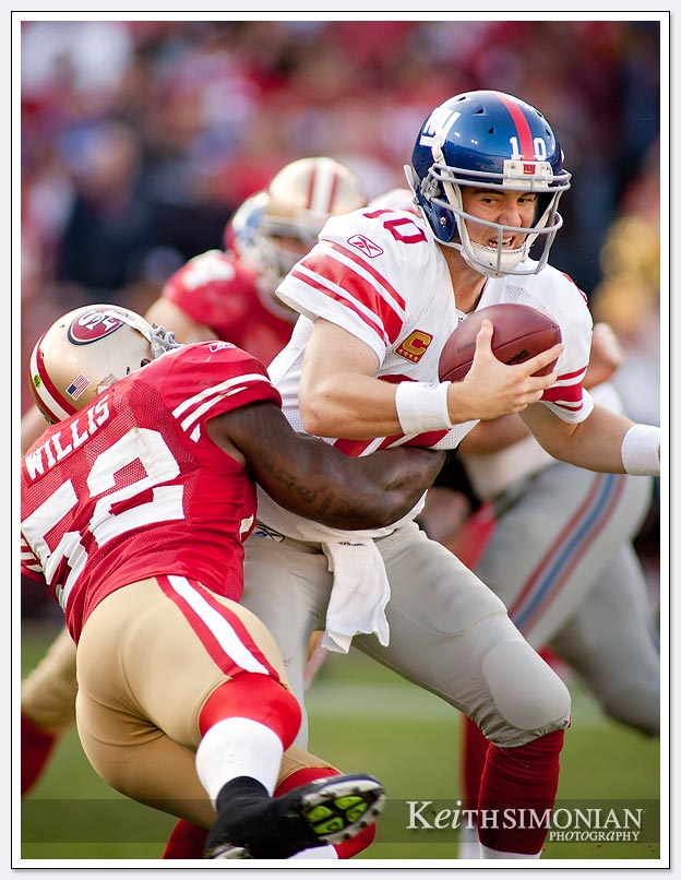QB Eli Manning is sacked by Patrick Willis